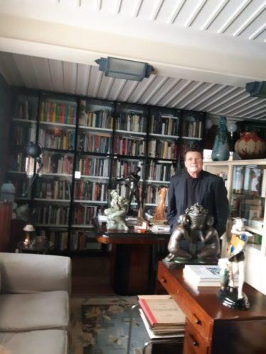 Estante com arte. No primeiro plano um homem com terno e ao fundo uma estante em madeira com portas de vidro, repleta de livros