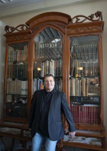 Estante com arte. No primeiro plano um homem com terno escuro e o fundo, armário-vitrine Art Nouveau,repleta de livros