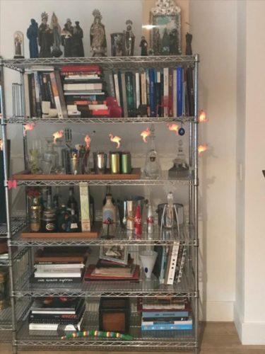 Estante com arte. Foto de uma estante de ferro cromado com livros, garrafas e coleção de santos