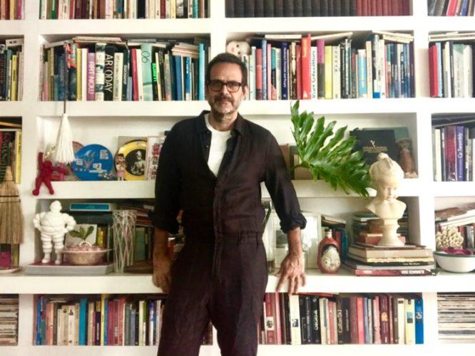 Estantes com arte. Alberto Renault ( com barba e óculos) em frente a uma estante branca, com vários nichos e repleta de livros