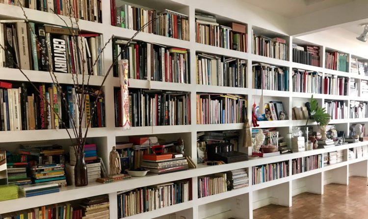 Estantes com arte. Foto de uma estante ocupando uma parede grande. Estante branca, com nichos, repleta de livros e alguns objetos.