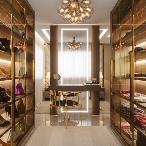 Sofisticação em apartamento com 100m². Closet com armários dourados com vidro e iluminação