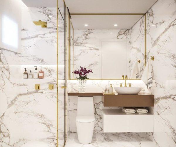 Sofisticação em apartamento com 100m². Banheiro todo revestido em mármore branco com veios marrons e detalhes dourados