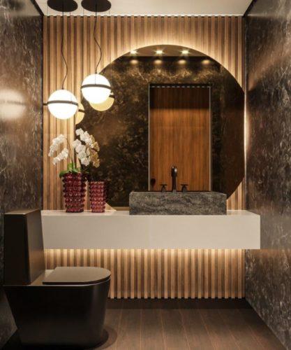 Sofisticação em apartamento com 100m² Lavabo com bancada em corian branco e parede de fundo ripado em madeira