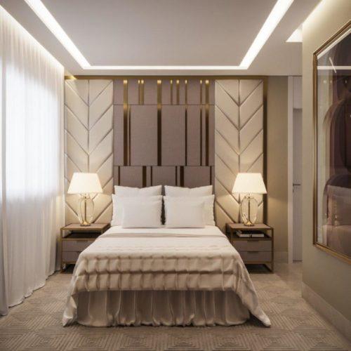 Sofisticação em apartamento com 100m². Quarto casal com cabeceira até o teto com detalhes dourados e carpete bege,