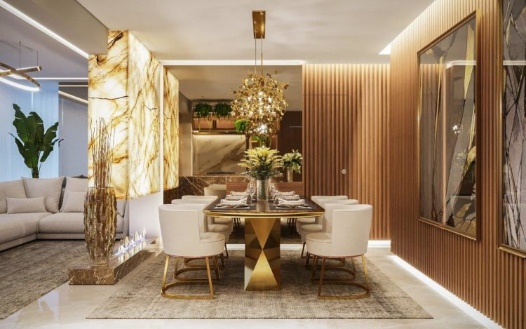 Sofisticação em apartamento com 100m². Sala de jantar com mesa dourada, painel em mármore e paredes com madeira ripada