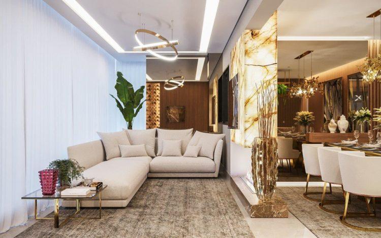 Sofisticação em apartamento com 100m². Painel em mármore e sofá bege na entrada
