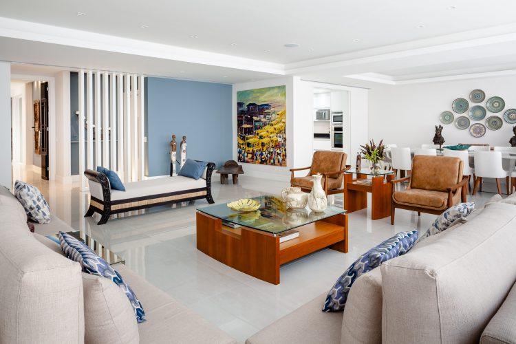 Apartamento da década de 60 passa por modernização. Sala ampla e clara, piso branco, sofás da cor cru, mesa de centro madeira clara e ao fundo uma parede pintada de azul claro