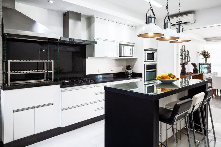 Apartamento da década de 60 passa por modernização. Cozinha moderna, com ilha central em granito preto. Bancada atras com cooktop, churrasqueira e armários brancos.
