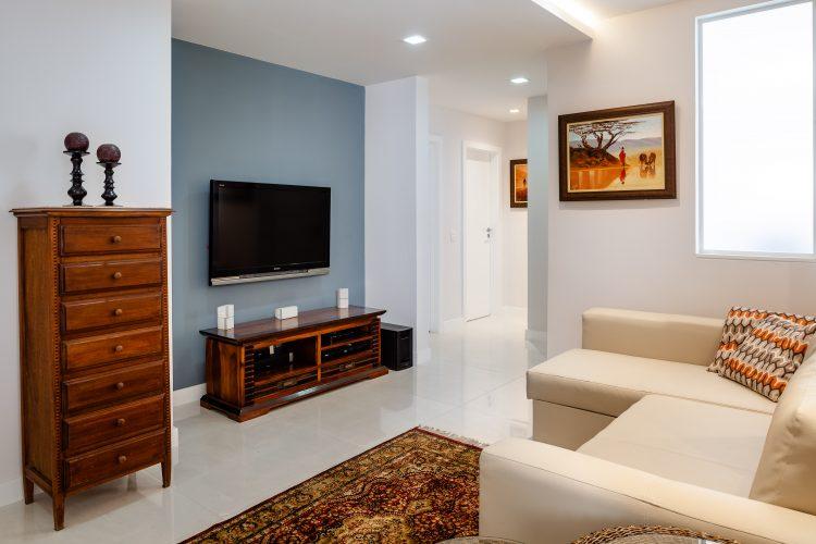 Apartamento da década de 60 passa por modernização. Tv na parede com fundo azul claro e sofá bege em frente