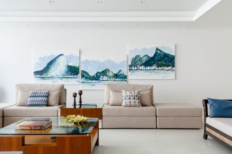 Apartamento da década de 60 passa por modernização. Composição de três quadros em aquarela retratando o rio, pendurados irregularmente na parede branca com um sofá cru em frete.