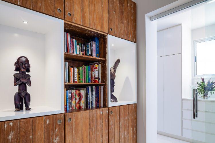 Apartamento da década de 60 passa por modernização. Esculturas africanas em um nicho branco na estante de madeira