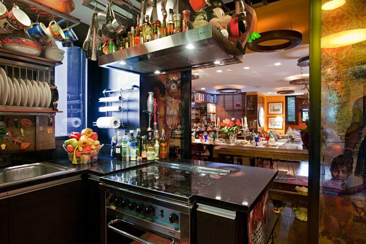 Cozinhas com estilo. Cozinha da casa do arquiteto Chicô Gouvea, aberta para a sala, com coifa em cima do fogão repleta de temperos