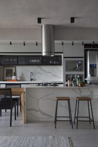 Cozinha com estilo. Essa cozinha totalmente integrada para a sala com ilha central em porcelanato imitando mármore e ao lado uma mesa de madeira