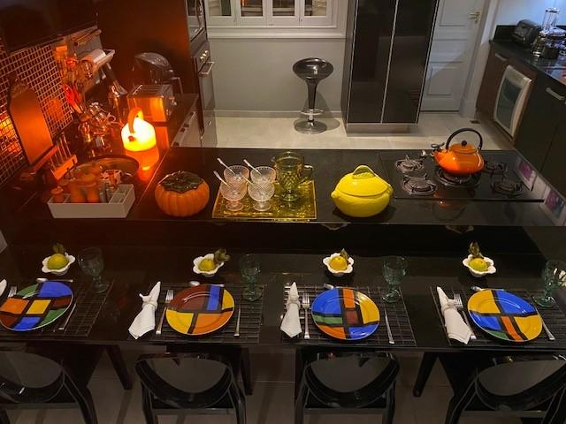Cozinha com estilo. Cozinha ampla com uma ilha em L, bancadas pretas e armarios em madeira, paredes pintadas na cor cinza azulado. Bancada com duas alturas , a mais baixa servindo como mesa. Cadeiras pretas e louça colorida