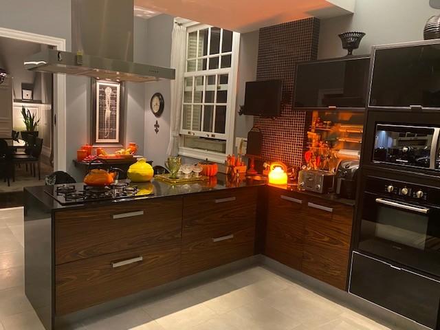 Cozinha com estilo. Cozinha ampla com uma ilha em L, bancadas pretas e armarios em madeira, paredes pintadas na cor cinza azulado. Forno e microondas embutido.