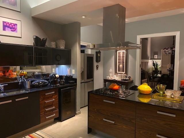 Cozinha com estilo. Cozinha ampla com uma ilha em L, bancadas pretas e armarios em madeira, paredes pintadas na cor cinza azulado