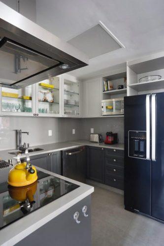 Cozinha com estilo. Bancada em silestone cinza , armarios superiores com porta em vidro transparente e inferiores na cor azul.