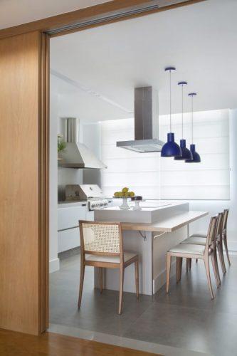 Cozinha com estilo. Cozinha tada branca, com ilha no meio em silestone com mesa em madeira acoplada