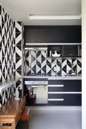 Cozinha com estilo. Cozinha revestida com azulejos com desenho gráfico nas cores preto e branca. Armários pretos e bancada branca