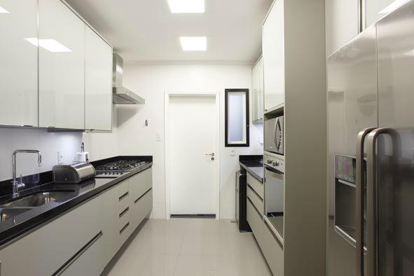 Cozinha com estilo. Cozinha com planta tipo corredor, bancadas pretas e todos os armários brancos sendo que os de cima em vidro branco leitoso, eletrodomésticos em inox e torre com forno e microondas embutido