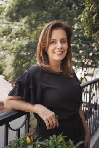 Imagem de uma mulher com blusa preta encostada na sacada de um avaranda