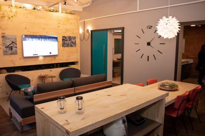 Consumo consciente: o que muda no modo de morar depois da quarentena. Interior de uma casa com painel da tv em madeira pinus e bancada da cozinha yb