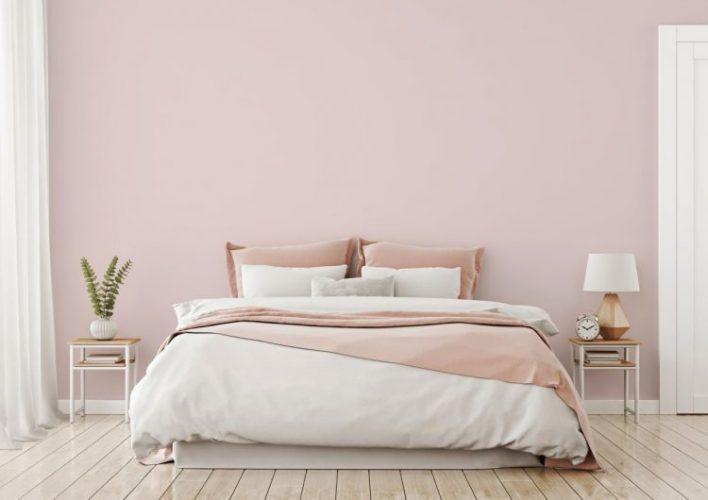 Tintas Eucatex dá dicas sobre como as cores podem influenciar o humor na quarentena. Quarto com a parede de fundo pintada de rosa clarinho,cortinas brancas e cama de casal com lençóis branco e rosa