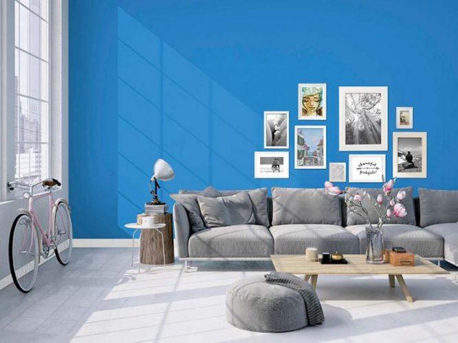 Tintas Eucatex dá dicas sobre como as cores podem influenciar o humor na quarentena. Um sala clara, com janelas altas, a parede de fundo do sofá cinza está pintada de azul e com uma composição de quadros na parede.