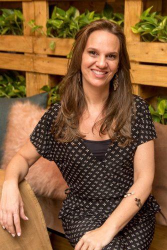 Consumo consciente: o que muda no modo de morar depois da quarentena. Foto de uma mulher sorrindo com vestido preto e atras plantas