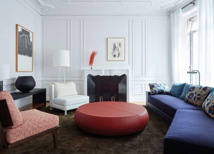 Loja Christian Liaigre em Paris. Sala com paredes brancas e boiserie. Lareira, sofá zaul, no centro um puff redondo vermelho