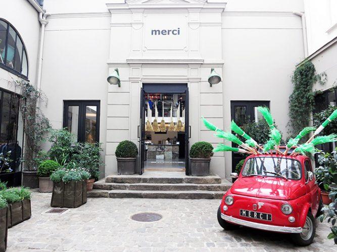 Loja Merci, Marais - Paris. Fachada da loja em predio antigo, tres degraus com topiarias ao lado e na frente um mini carro vermelho antigo