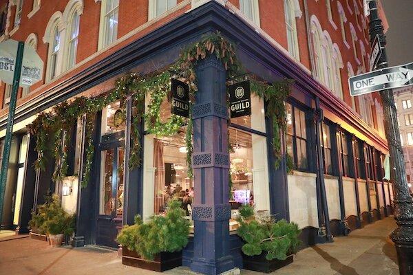RW Guild, 53 Howard St, New York, NY. Fachada da loja ocupando um esquina. Construção pequena charmosa pintada de azul e planta na frente