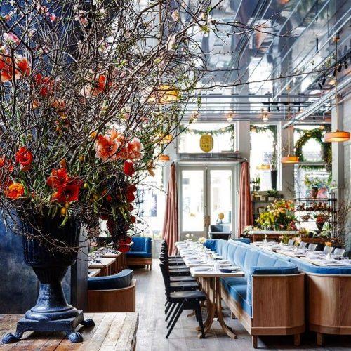Restaurante Mercerie,na RW Guild. Ambiente sofisticado do restaurante com sofá azul