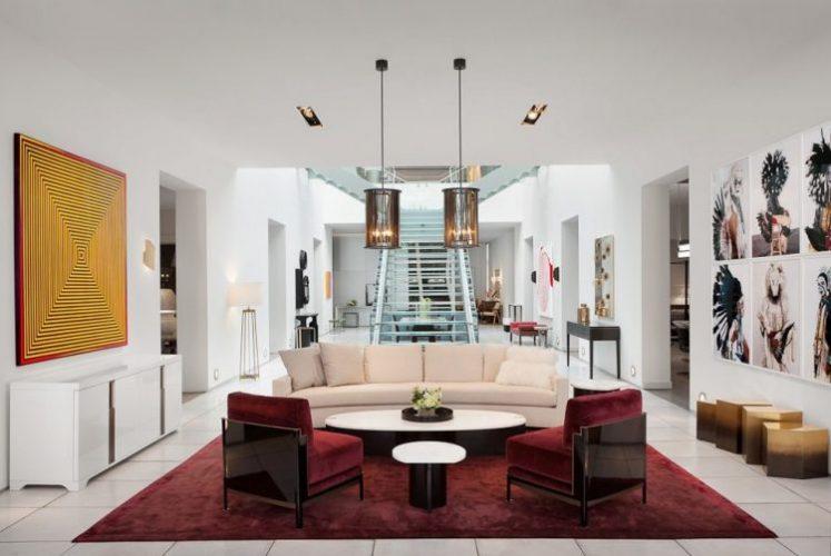 Showroom da Loja Holly Hunt Miami. Ambiente de sala com um sofáoval branco,uma serie de qaudros na parede