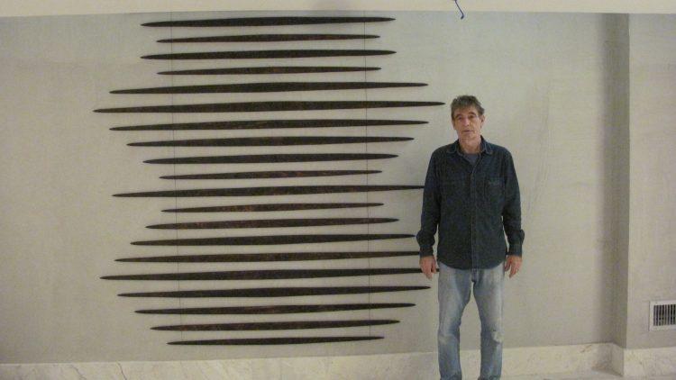 Sementes de sucesso, artista plastica Monica Carvalho que usa sementes no seu trabalho. Foto de um homem e frente a um mobili de madeira