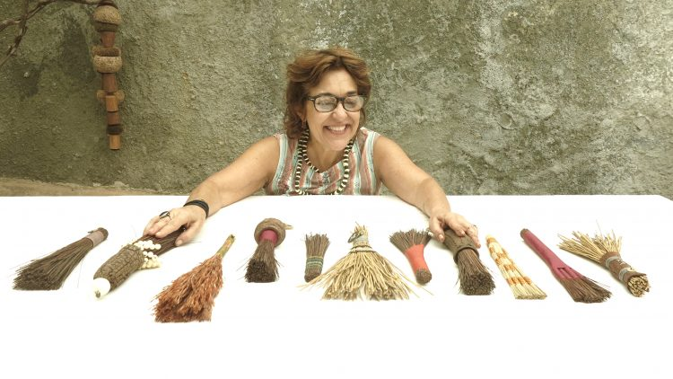 Sementes de sucesso, artista plastica Monica Carvalho que usa sementes no seu trabalho. Foto da artista plástica em frente a uma mesa com varias mini vassourinhas de cipo