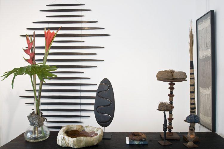 Sementes de sucesso, artista plastica Monica Carvalho que usa sementes n seu trabalho. Foto de um móbili de madeira na parede e em cima da mesa esculturas