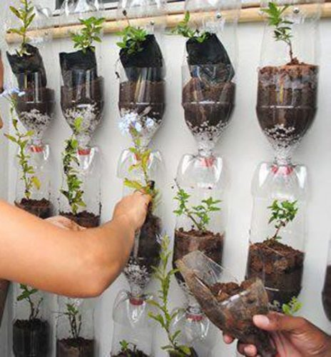 Transforme (parte da) sua sacada em uma horta. Garrafas pets com ervas plantadas, penduradas no muro