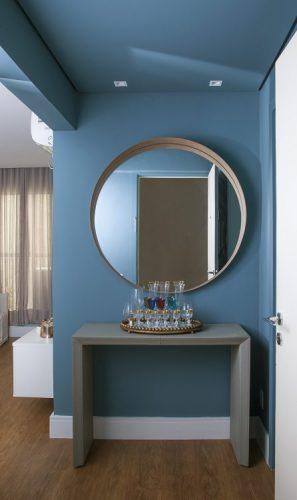 Apartamento de 40 m² com soluções para sua pequena metragem. Hall de entrada com as paredes pintadas de azul e espelho redondo em cima da aparador