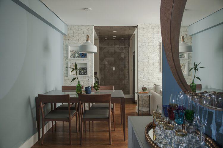 Apartamento de 40 m² com soluções para sua pequena metragem. Sala com a mesa de jantar em madeira enconstada na parede pintada de azul