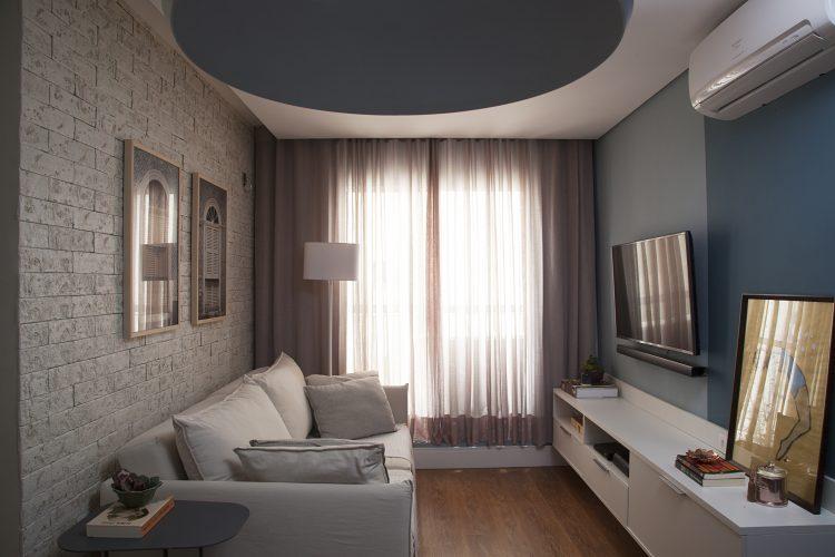 Apartamento de 40 m² com soluções para sua pequena metragem. Sala de estar com parede de tijolinho com sofá branco na frente. Na outra parede, pintada de azul com a tv na parede