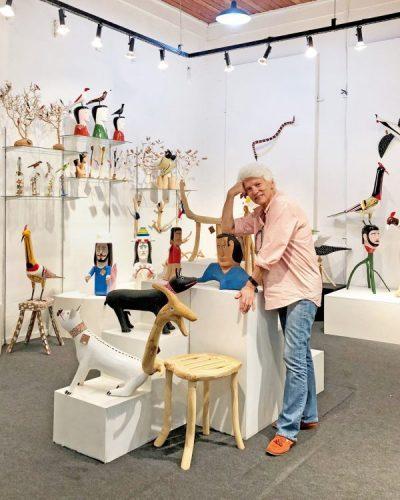 loja de arte popular brasileira, com a foto da dona da loja no meio. Paredes brancas e objetos em madeira colorido.