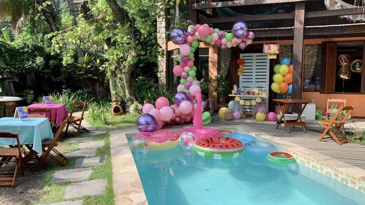 No jardim de uma casa, bolas coloridas, boias de flamingo na piscina