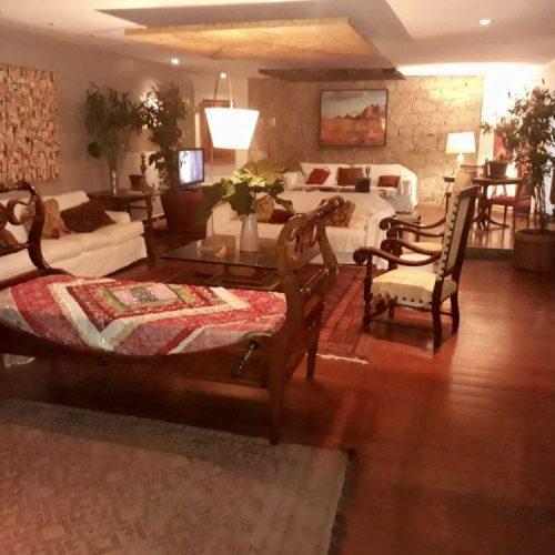 interior de uma casa com parede de pedra e moveis em madeira
