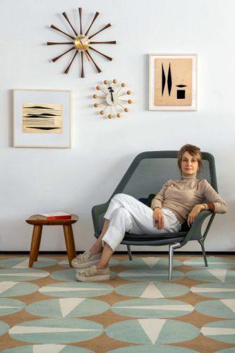 Coleção de tapetes inspirada na obra de Noel Marinho. Mulher sentada em uma cadeira em cima de um tapete com circulos azul claro, peças de design.