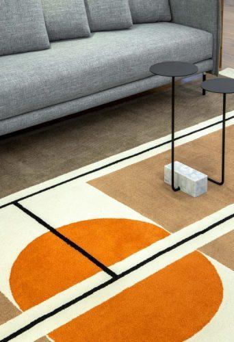 Coleção de tapetes inspirada na obra de Noel Marinho.Tapete bege, com circulo laranja e traços pretos