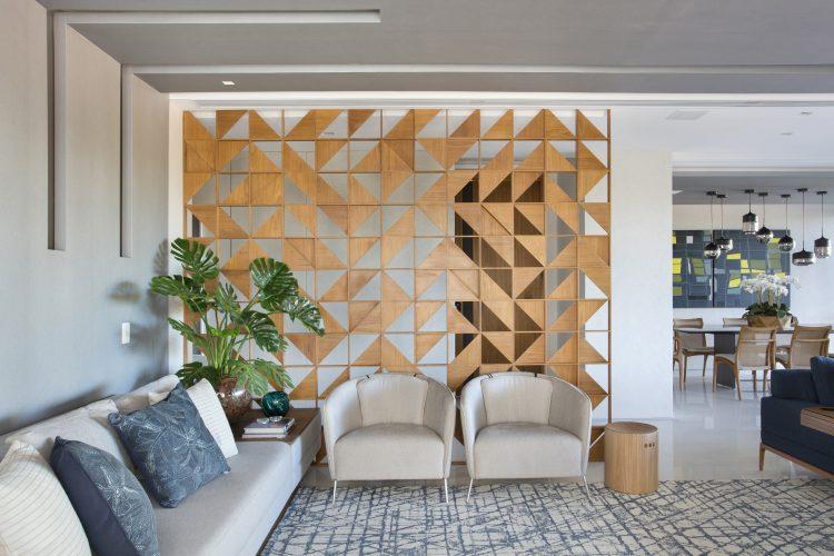 APARTAMENTO COM DÉCOR LEVE. Um painel em madeira clara com elementos vazados criando triaangulos, separa a entrada da sala.