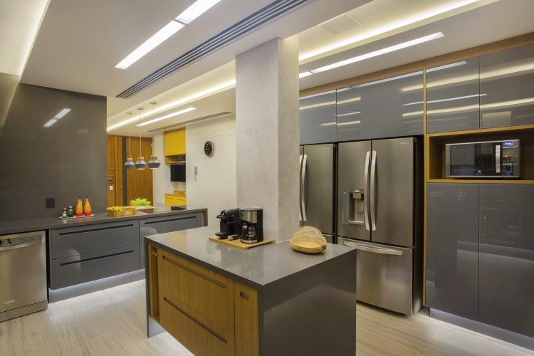 APARTAMENTO COM DÉCOR LEVE. Cozinha com armarios na co cinza e cimento queimado nas paredes.