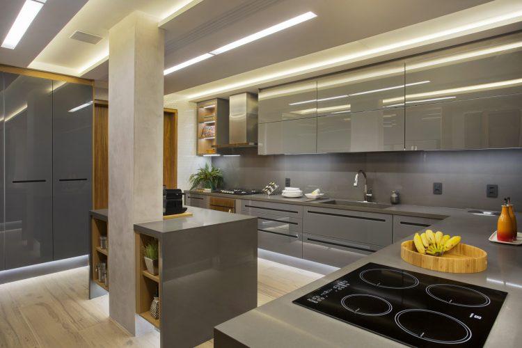 APARTAMENTO COM DÉCOR LEVE. Cozinha com armarios na cor cinza e parede em cimento queimado.